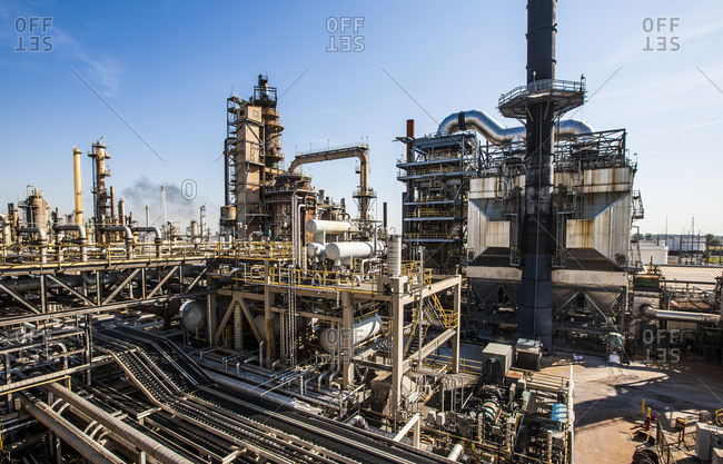 High angle view of oil refinery against blue sky during sunny day