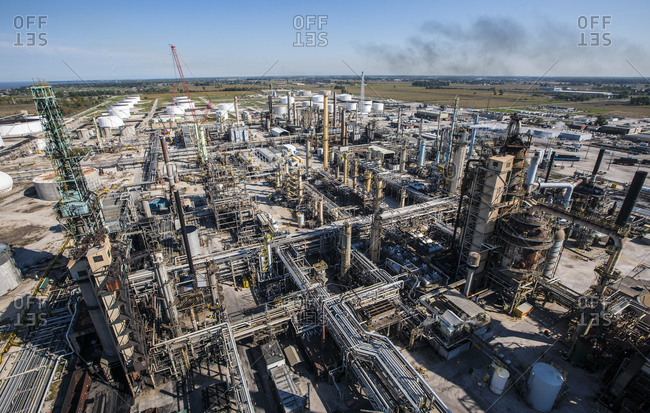 High angle view of oil refinery against sky during sunny day