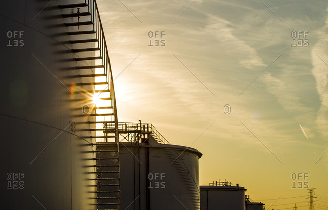 Low angle view of storage tanks at oil refinery against sky during sunset