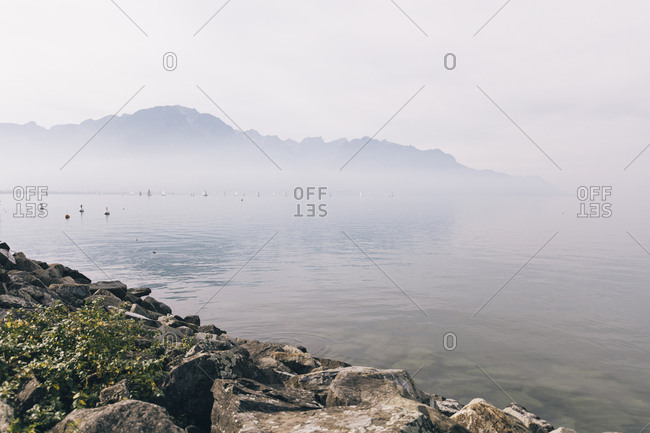 Scenic view of lake by mountain against sky during foggy weather