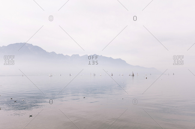 Scenic view of lake by mountain during foggy weather