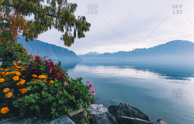 Tranquil scene of lake by mountains against cloudy sky