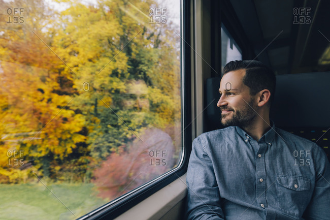 Smiling man looking through window while traveling in train
