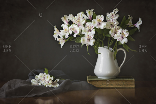 Peruvian lilies in vase with book and fabric on wooden table
