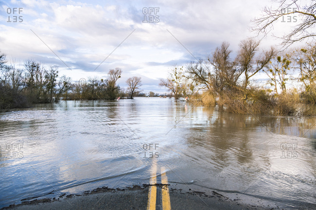 Flooded road against cloudy sky