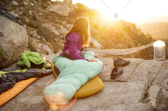 Woman in sleeping bag looking away while relaxing on rock