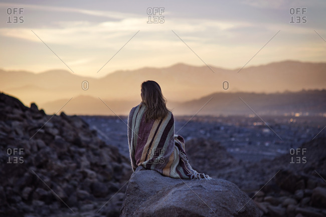 Rear view of woman wrapped in blanket sitting on rock against sky