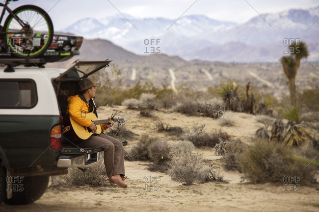 Man playing guitar while sitting on car trunk