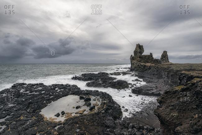 Scenic view of rocky coastline against cloudscape