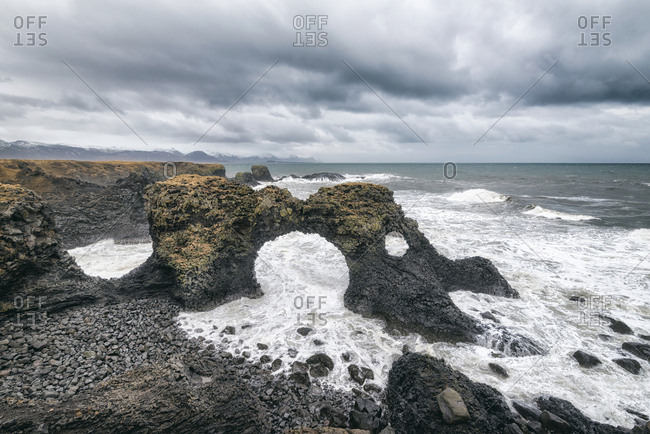 High angle view of rock formations in sea against cloudscape