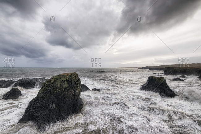 Sea waves rushing amidst rocks against cloudy sky
