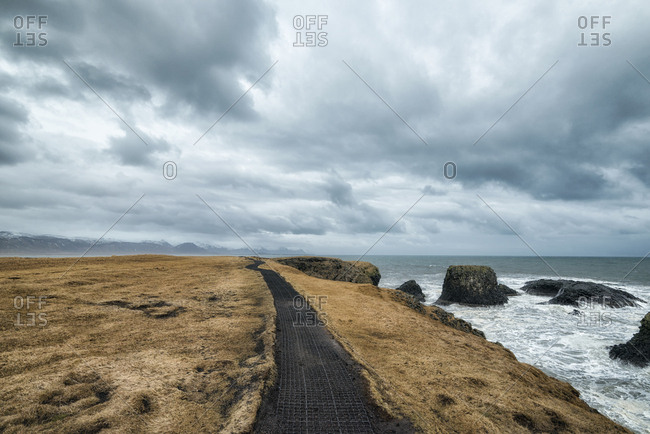 Footpath on mountain by sea against cloudscape