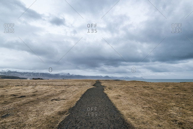Pathway amidst field against cloudscape