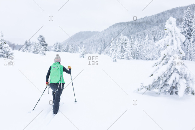Rear view of female hiker hiking on snow covered field