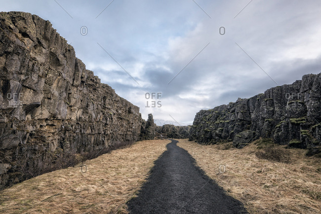 Empty pathway amidst rocky cliffs against cloudy sky