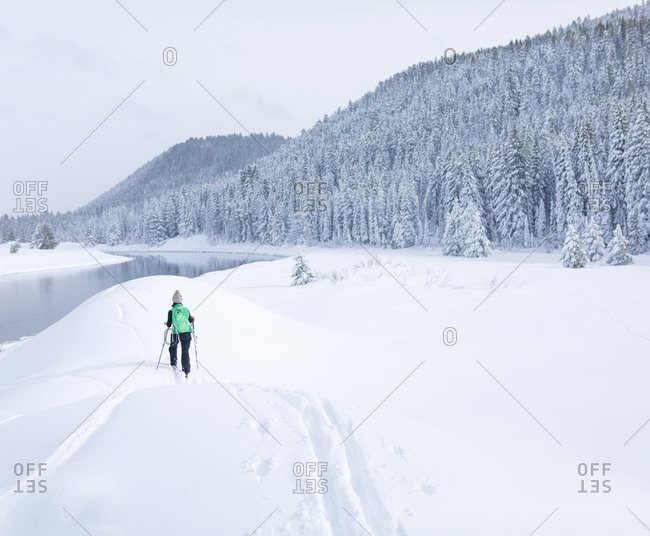 Rear view of female hiker hiking on snow covered field against sky