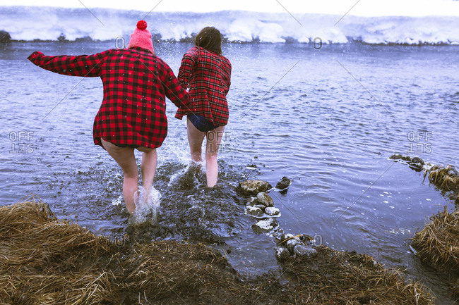 Rear view of female friends enjoying in lake during winter