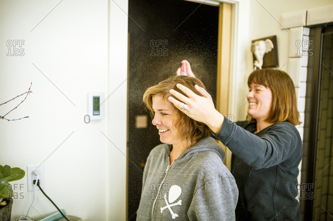 Woman using hairspray on sister's hair