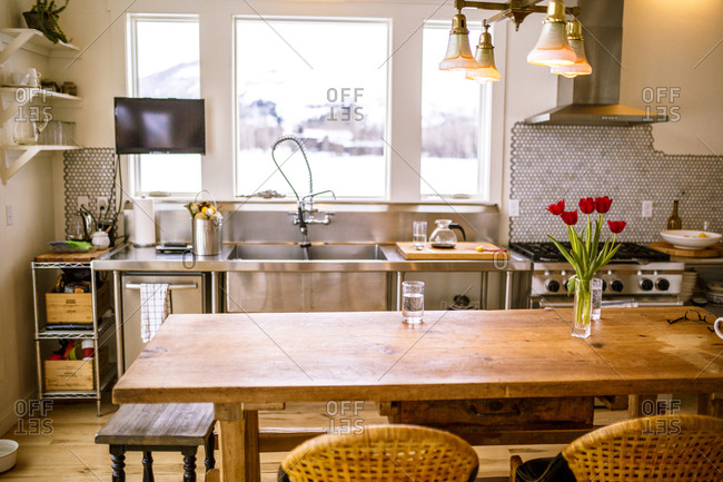 Empty chairs at table by kitchen counter at home
