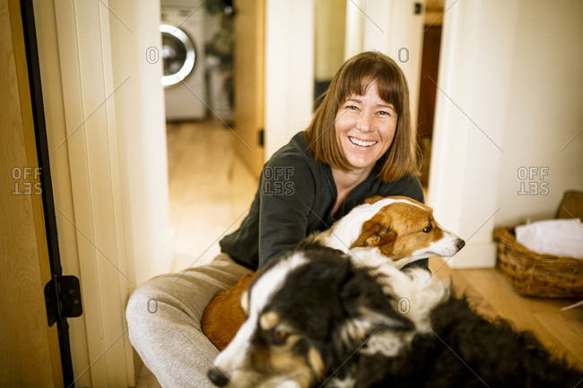 Portrait of woman with dogs sitting on floor at home