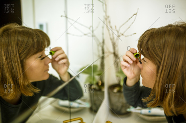 Close-up of woman applying mascara while reflecting in mirror at home
