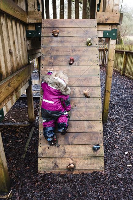 Rear view of girl rock climbing at park during rainy season