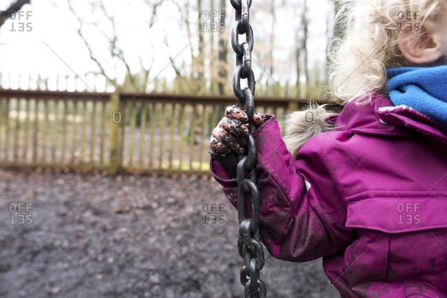Cropped image of girl with muddy hand playing on swing at park during rainy season