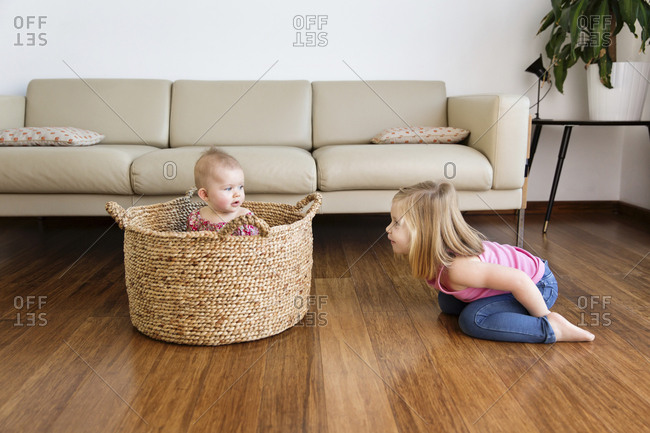 Playful girl looking at sister sitting in basket at home