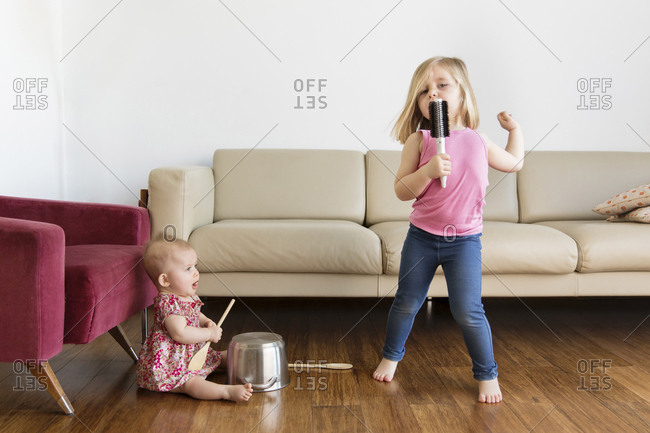 Portrait of girl singing into hairbrush while sister playing with spoons and bowl at home