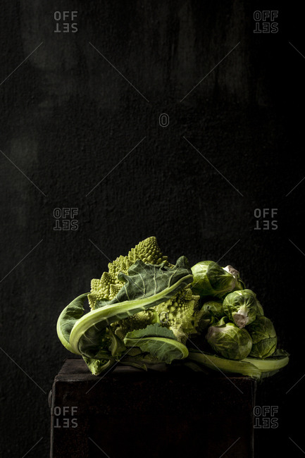 Close-up of Romanesco Cauliflower with Brussels sprouts on wooden table against black background