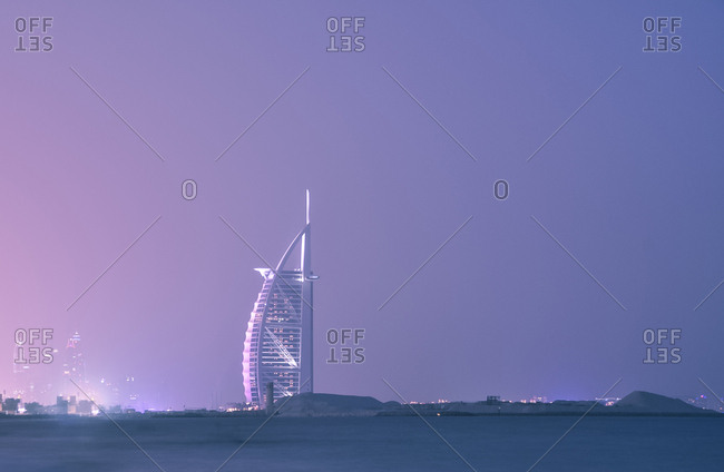 United Arab Emirates, Dubai - August 17, 2013: Illuminated Burj Al Arab Hotel by sea against clear sky at dusk
