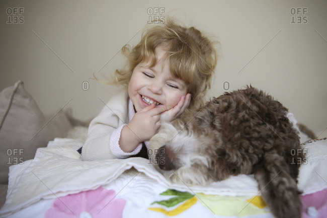 Happy girl relaxing with dog on bed at home