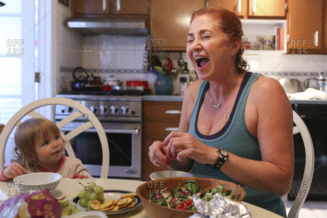 Cheerful grandmother preparing food while sitting with granddaughter at table