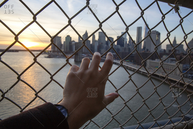 Cropped hand of man holding chainlink fence against one world trade center