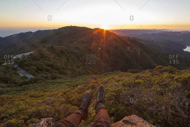 Low section of man sitting on rocks against mountains against sky
