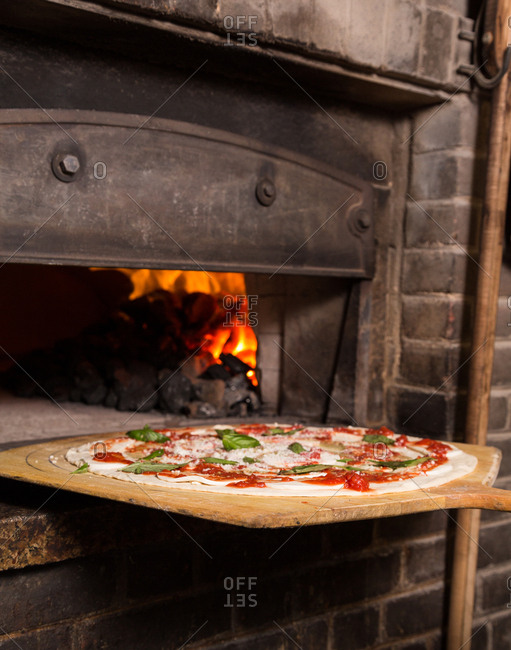 Freshly made pizza going into a coal fired oven