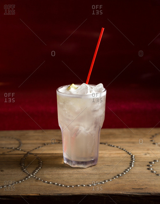 Vodka tonic cocktail with red straw on rustic wood surface
