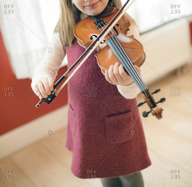 Girl practicing violin during private workshop.