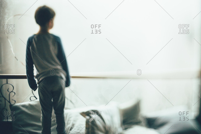 Little boy standing on cushions in a bright light