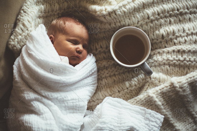 Swaddled sleeping baby next to a cup of tea