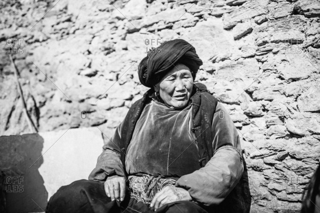1/29/17 - Senior Qiang woman sitting against a stone wall in a rural village