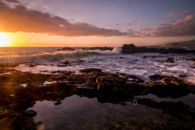 Waves crashing on rocks and tidal pools on a shore at sunrise