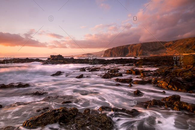 Foamy water flowing over rocks on a coast at sunrise