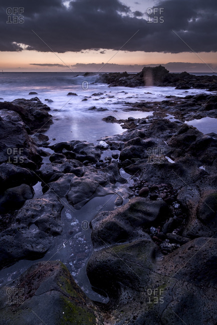 Water flowing between rocks on a shore at sunset