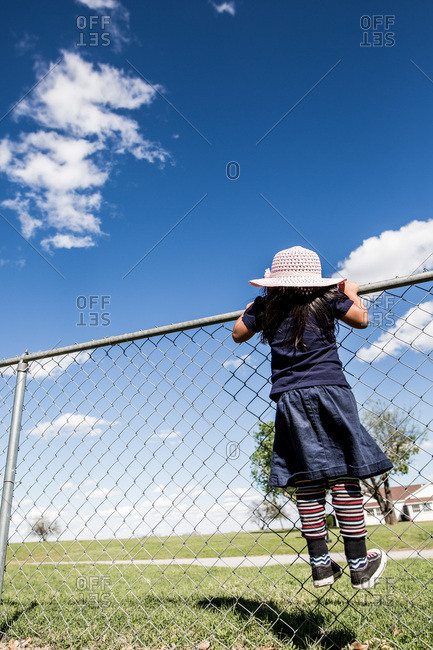 Girl wearing a pink hat peering over chain link fence