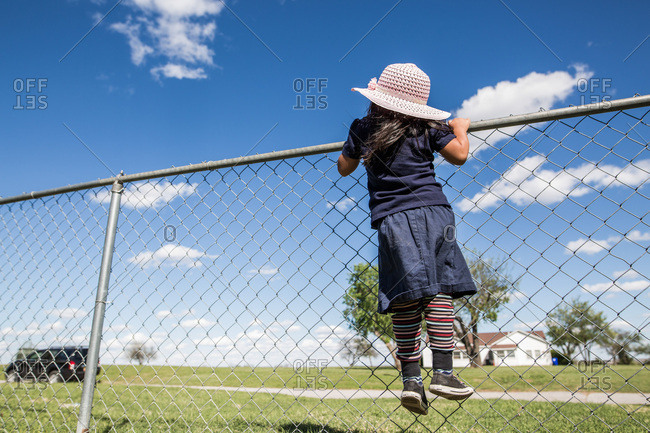 Girl wearing a pink sun hat looking over top of fence