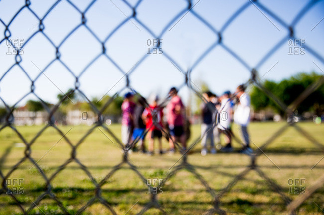 Baseball team standing behind chain link fence