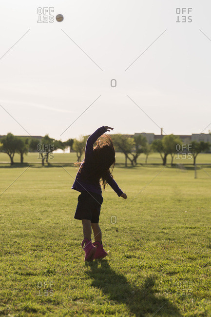 Girl tossing a baseball high into the air