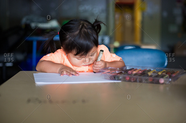 Little girl drawing picture on sheet of paper with crayon