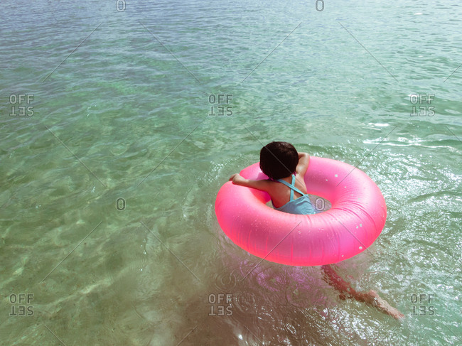 Girl swimming in a pink inflatable ring